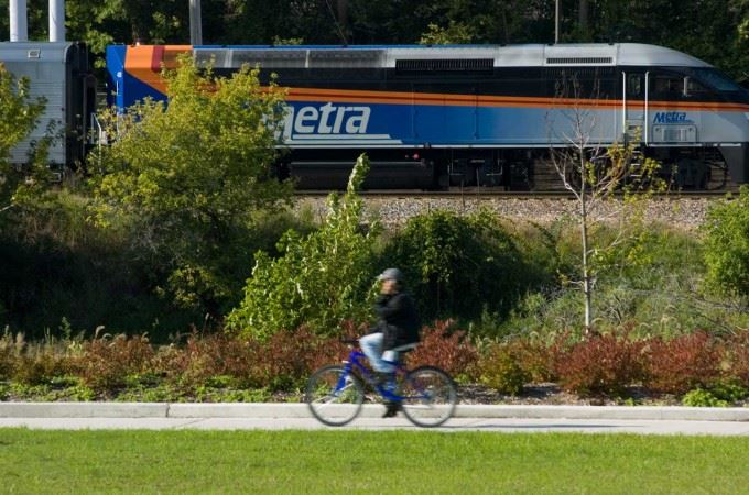 Biker along Fox River Trail with a Metra train in the background